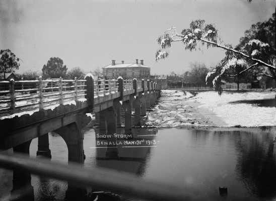 Snow storm in Benalla - 31st May 1913.  A view across the concrete reinforced road bridge over the Broken River, looking towards Benalla East. Fallen snow is visible. The Benalla Post and Telegraph Office is in the background. William John Howship (1874-1932) opened a photography studio business in Nunn Street Benalla in April 1904. He expanded the business by selling small format Kodak […]