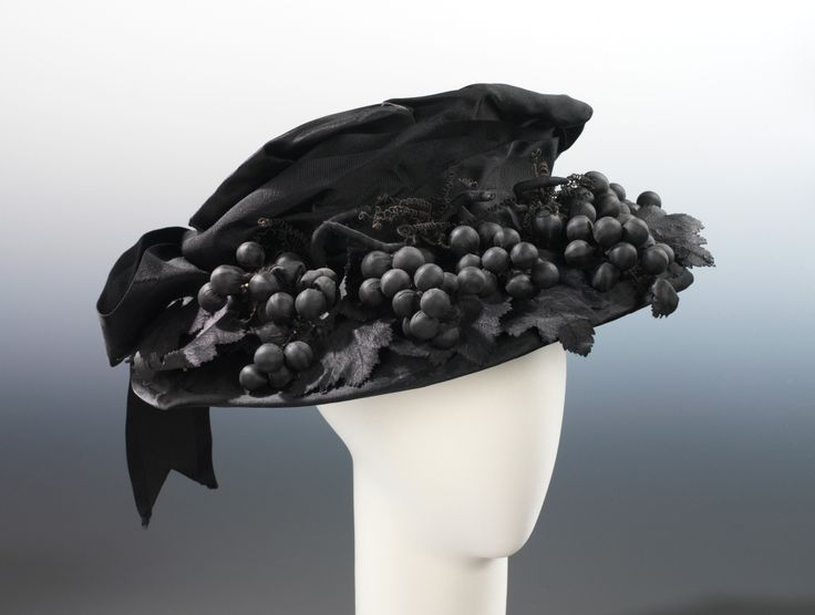 """Mourning Hat, Bruat, Inc.: ca. 1915, American, silk. """"Black hats were popular for general wear in the 1910, particularly during the years of World War I, when sobriety and utility were the order of the day. Some hats, however, stand out specifically as mourning wear...despite how chic the design might be...the unrelieved black clearly identifies its function. The choice of grape clusters...produces an incongruous shock, thereby serving to strengthen the statement of mourning."""""""