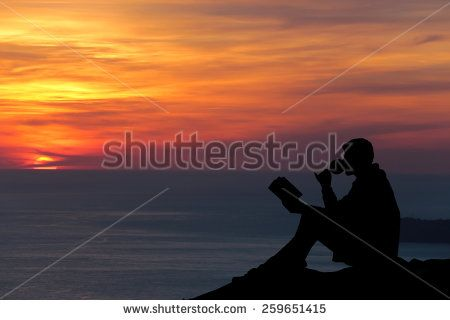 Silhouette of a man sitting on breakwater in evening near sea, reads book  and drink wine - stock photo