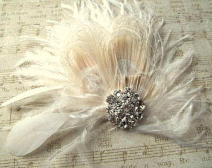 Wedding Bridal Fascinator This gorgeous bridal fascinator is appx 3.5 inches high It is made from ivory ostrich feather background with bleached ivory peacock accent feathers, curled ivory ostrich feathers, stripped nagoire feathers, hand curled hackle feathers. with a sparkling 1 inch rhinestone jewel! It is attached to a metal alligator clip on back for security and ease of placement. You can wear this piece on the side or back, with a french net veil (sold seperately in my shop) This…