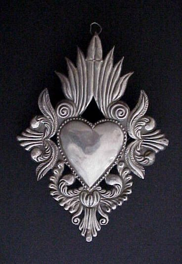 Vintage Sacred Heart Milagro, Ex Voto | This is a beautiful old South American sterling silver milagro, or ex voto from the early part of the 20th century. | The ex voto was left in a church in Peru by a pilgram or devotee giving thanks for his or her wish fulfilled. This large milagro, formed from one sheet of silver, is in the shape of the sacred heart and decorated with traditional Spanish colonial foliate designs in deep repoussé.