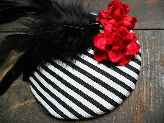 Beautiful fascinator hand stitched by Miss Moss! This piece is made from a round fascinator hat base, covered with black and white striped cotton fabric. Finished with gorgeous black feathers and 2 red paper roses. Fixed with a plastic hair slide and metal clip Size: Diameter: 10cm