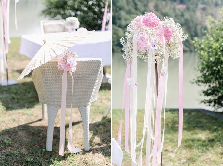 Rosa-weiße Blumendeko mit Bändern bei einer Trauung unter freiem ...