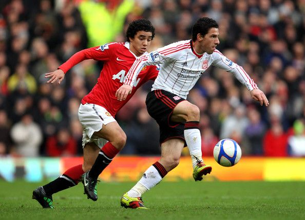 Rafael of Manchester United competes with Maxi Rodriguez of Liverpool during the FA Cup sponsored by E.ON 3rd round match between Manchester United and Liverpool at Old Trafford on January 9, 2011 in Manchester, England.