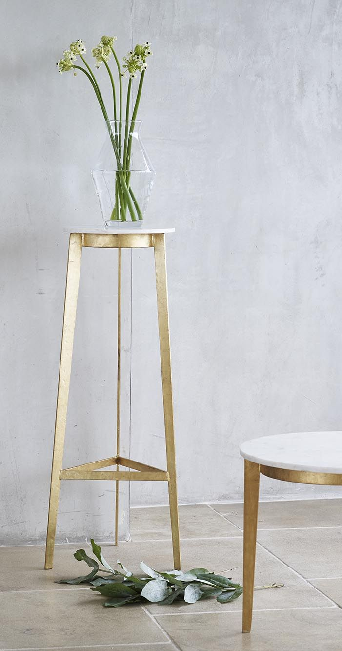 Create a clean and minimal aesthetic with the sleek silhouette of our marble-topped round side table with slim tapered gold legs.