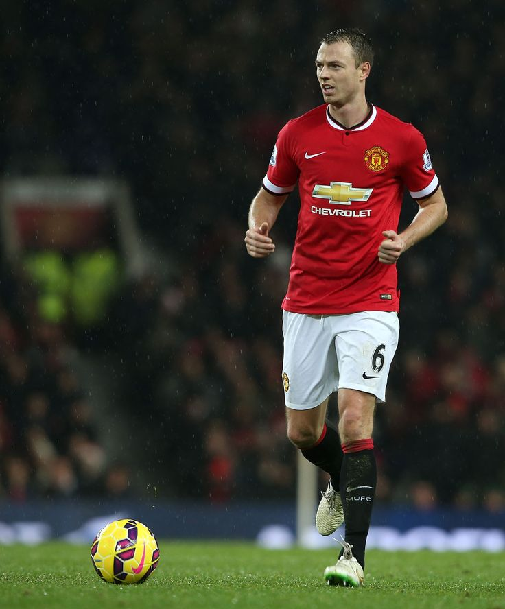 Jonny Evans brings the ball out of the defence wearing the @manutd home shirt.