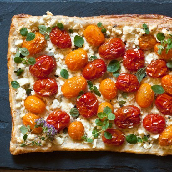 Cherry tomatoes, feta cheese, and fresh oregano on a puff pastry crust make a simple vegetarian tart perfect for brunch.