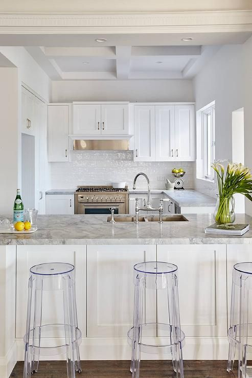 Gorgeous white kitchen boasts clear acrylic counter stools placed on wide oak wood floors in front of a white peninsula topped with a Super White Dolomite countertop fitted with a stainless steel dual sink and a polished nickel gooseneck faucet.