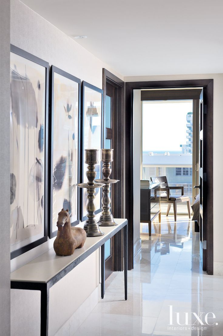 A narrow Christian Liaigre console from Holly Hunt creates horizontal continuity in the hallway leading to two bedrooms; its length broken up by a botanical triptych. Tall patina brass candleholders draw the eye to the vertical elements of the space.