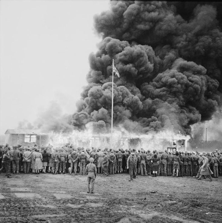 Crowds watch the destruction of the last hut at Belsen two days after the camp was finally evacuated. The hut was set on fire by a British flamethrower.