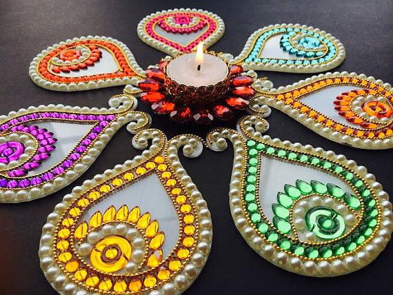 This rangoli would have a total of seven pieces which can be arranged as you'd like. This has 7 Kalash shaped pieces and candle holder in center.