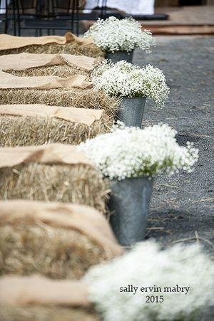 Beautiful rustic wedding idea! Hay bale seating covered in burlap, with baby's breath in sap buckets for aisle way decor during your ceremony. All decor is from Sassifras Design at The Lodge!