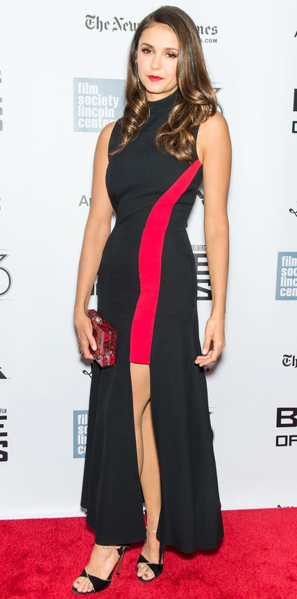 Nina Dobrev accentuated her curves at the Bridge of Spies premiere in a sleek black gown with a curved red panel that ended with a thigh-high slit.