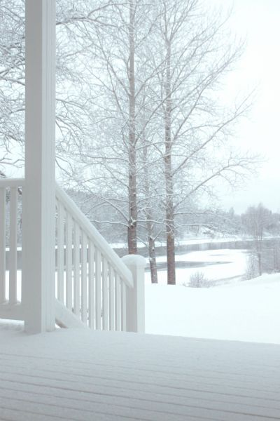 White wood house with snow...
