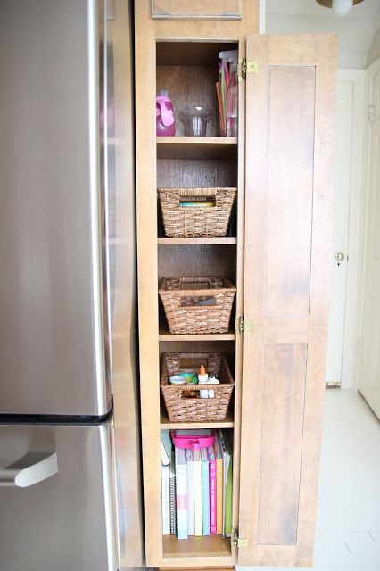 Skinny tall cabinet next to refrigerator Put cookbooks