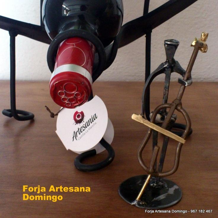 Figura de un músico tocanddo el violonchelo hecho con clavos de herrar, junto a una botella de vino sobre un botellero artesano.