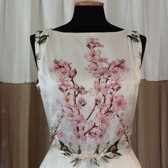 """Close-up di abito impreziosito da un cinturino con piccole applicazione floreali,  tutto  realizzato a """"mano""""."""