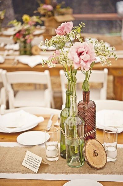 Vineyard wedding table decorations...love the green bottle, clear bottle and burlap.  Not so much the way the flowers are arranged.