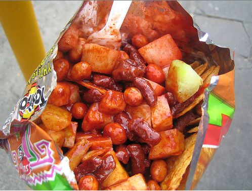 """Tostilocos (also Dorilocos[1]) are a popular Mexican antojito (street food) that consists of tortilla chips topped with cueritos, cucumber, jícama, lime juice, Valentina hot sauce, chamoy, tajín chile powder, salt, and """"Japanese peanuts"""". mango pits added are the best"""