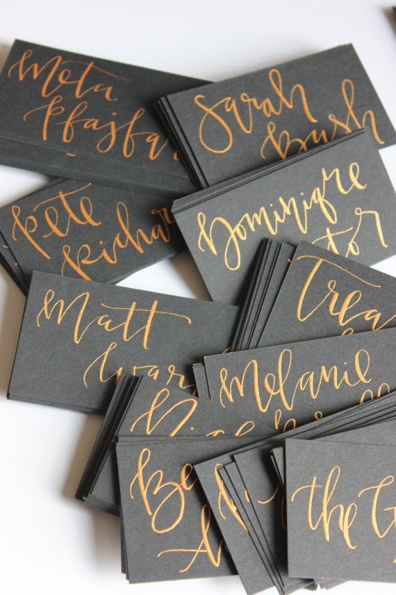 Black card stock escort card with gold calligraphy. Each card is hand lettered with your guests name and table assignment. Both flat and tent cards