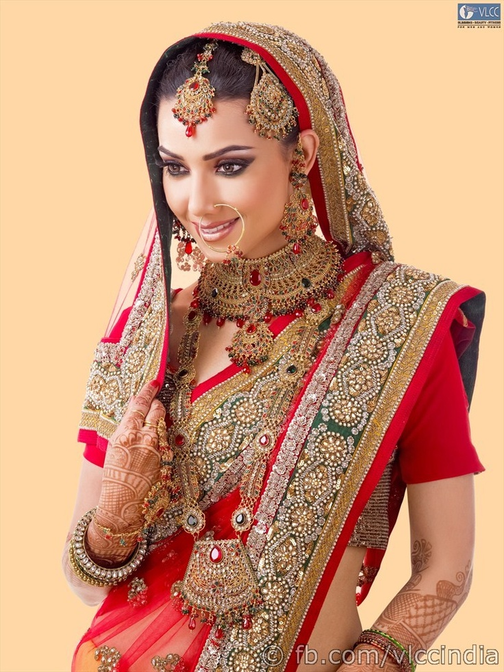 Decked up in gorgeous sari, gold necklaces, bangles and earrings, this bridal look leaves onlookers simply breathless. The eyelids glimmer with concentrated pigments while the eyes are lengthened with liner and shaped with kohl. The lips are coloured richly. The hair is adorned with traditional hair accessories or an elaborate upstyle.