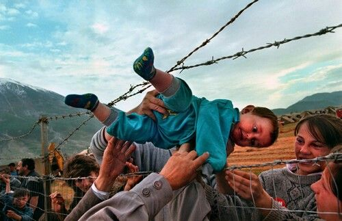 In 2000 Carol Guzy received a Pulitzer Prize for the touching photographs she had taken of the Kosovo refugees. In this particular photo, a 2-years-old refugee child was being passed through the barb wired fence to his family on the other side. Guzy currently works for the Washington Post and has won the Pulitzer four times.