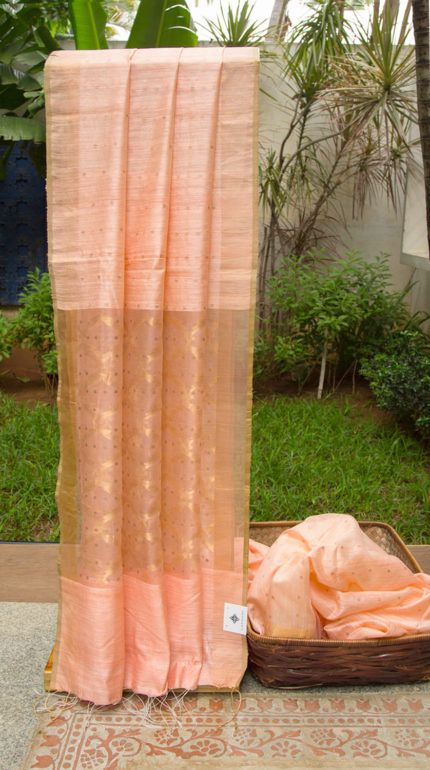 This delicate Bailou Matka Silk sari is in salmon pink with gold sequin work all over. The border is a solid band of gold zari while the pallu is in kora with a jali pattern in gold zari and simila…
