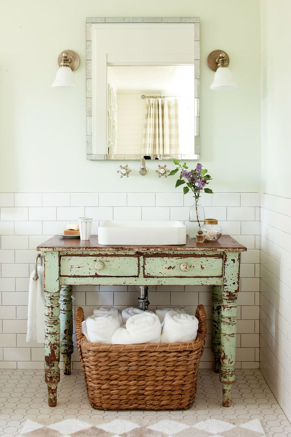 Give a new room instant age. A perfectly worn painted table breaks up the sea of white tile and carries on the farmhouse look.    Keep tile classic. White subway-style tiles by Daltile pair with octagonal tiles on the floor. The charcoal-colored grout remains true to the period style.  Coordinate your colors. Let an antique find inspire your wall color. The pretty pale green walls are painted Spinach White by Sherwin-Williams.  Be a basket case. Tuck extra storage into small rooms by…