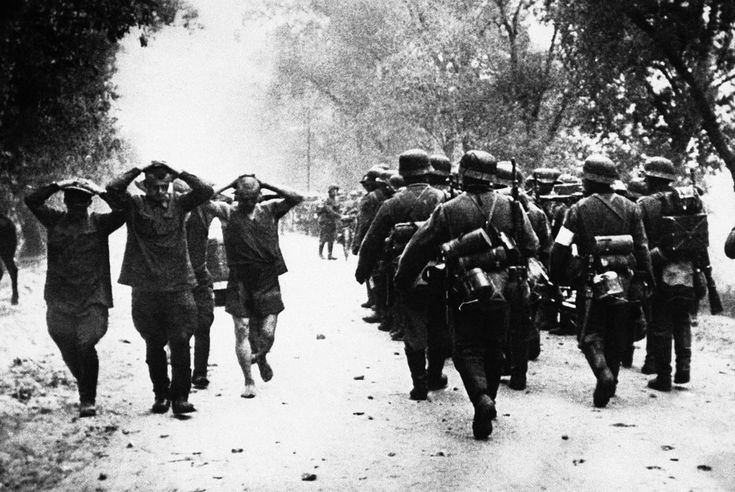 Russian soldiers, left, hands clasped to heads, marched back to the rear of the German lines on July 2, 1941, as a column of Nazi troops move up to the front at the start of hostilities between Germany and Russia.: