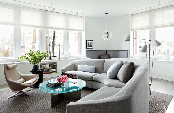 The living area in Julianna Margulies's Manhattan apartment, designed by Vicente Wolf, is anchored by a wraparound gray sofa and sleek cocktail table.   archdigest.com