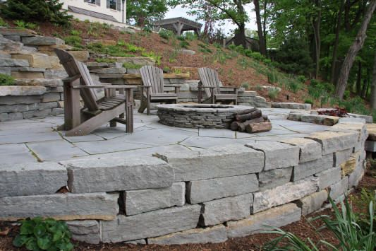 Stone retaining wall creates a cozy patio and firepit area along a hillside.