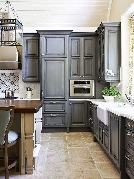 Charcoal-colored cabinetry brings stylish drama to this kitchen. - Traditional Home ® / Design: Design Galleria