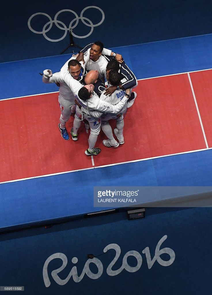 An overview shows France's team celebrating after winning the mens team epee gold medal bout between Italy and France as part of the fencing event of the Rio 2016 Olympic Games, on August 14, 2016, at the Carioca Arena 3, in Rio de Janeiro. / AFP / Laurent KALFALA