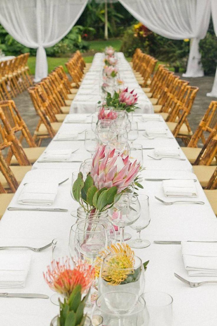 décoration florale pour table de mariage en automne - des fleurs des champs jaunes et orange en bocaux et fleurs de protea