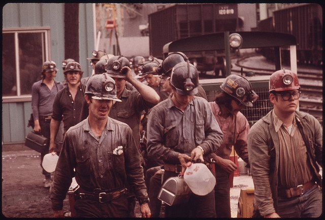 Original Caption: Miners Line Up to Go Into the Elevator Shaft at the Virginia-Pocahontas Coal Company Mine #4 near Richlands, Virginia the Man at the Right Wears a Red Hat Which Means He Is a New Miner and Has Worked Below Less Than a Month. His Belt Also Shows Less Wear Than the Others. The Miner at the Left Carries Red Man Chewing Tobacco, Used by Many of the Men Because They Cannot Smoke in the Mines. They Also Prefer to Carry Their Own Water Rather Than Use What the Company Provides…
