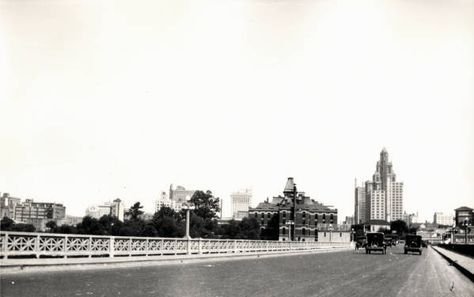 Houston skyline from a street level bridge. 1927. A view of the downtown Houston skyline looking east from an unidentified bridge. The bridge led into the downtown district between Capitol Avenue and Rusk Avenue. The Esperson Building is the tallest building seen in the photograph. George Fuermann 'Texas and Houston' Collection, 1836-2001. Special Collections, University of Houston Libraries (Public Domain).