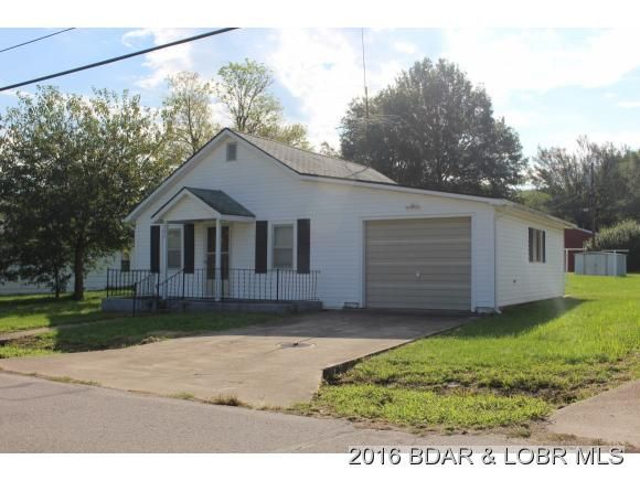 Great stater home or rental. Nice large lot with a double garage/workshop. Loads of potential.. Renovation has already started insulation, sheet rock, new wiring, unfinished oak cabinets ready to be installed also room to build. Call today!! in Versailles MO