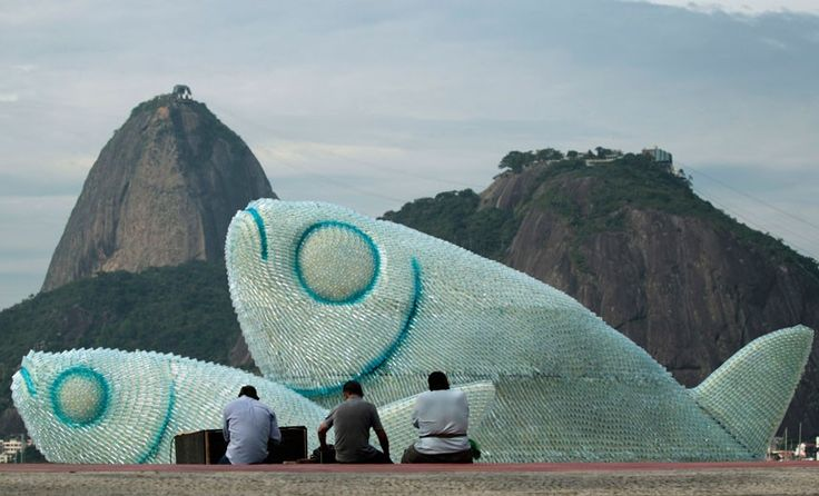 A fish sculpture constructed from discarded plastic bottles rises out of the sand at Botafogo beach in Rio de Janeiro, Brazil