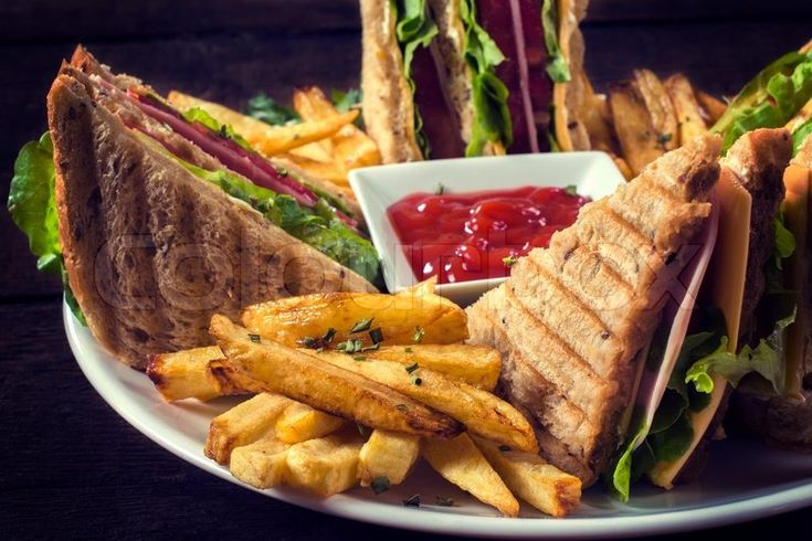 Delicious dinner for friends or family. Club sandwich and french fries with ketchup. Photography made by Bad Man Production. If you want to see more his amazing job, follow his portfolio here: https://www.colourbox.com/supplier/bad-man-production-103396