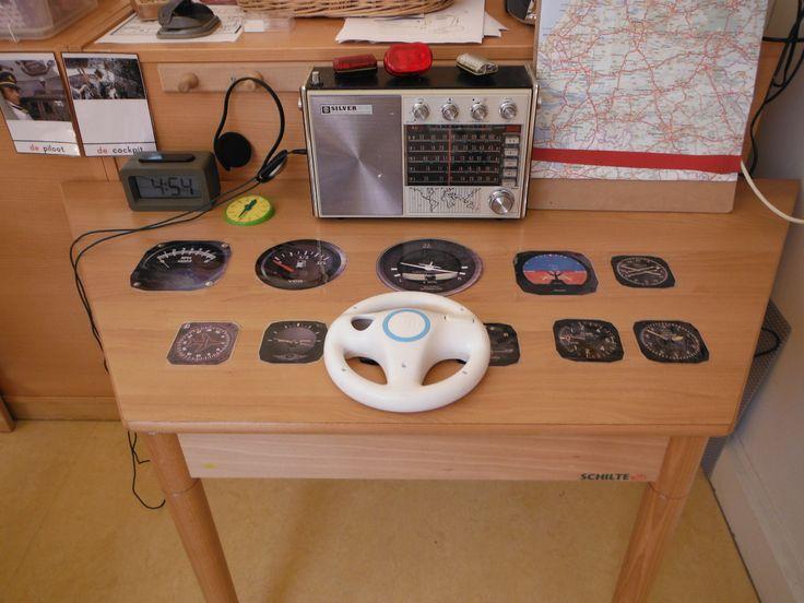 cockpit. oude radio met veel knopjes, gelamineerde geprinte klokken en metertjes, digitale wekker, wii stuurtje en vliegplan