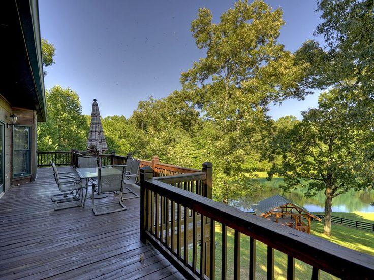 Просторная терраса с видом на задний двор и пруд.