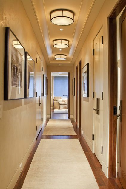A great way to address lighting in a hallway with a low ceiling is to create repetition using a flush-mounted ceiling light. This repetitive pattern can create interest and drama when you don't have the space for a larger fixture.