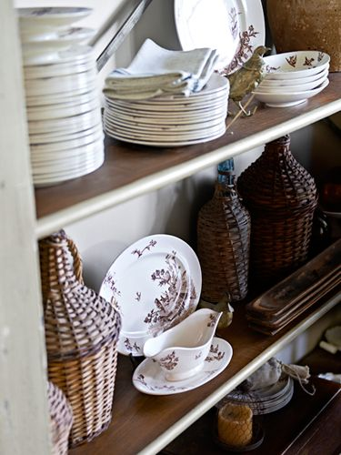 Pretty dining room vignette: love the dishes mixed with rattan and wood. comme dans ma boutique!