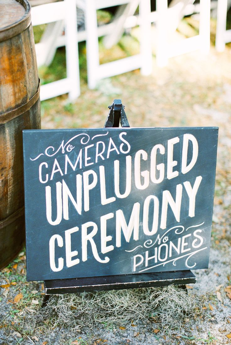 Unplugged ceremony sign, Southern pink, navy, and gold wedding. Gorgeous wedding details with Betsy Johnson heals, white rose bouquet, pink twist wrap bridesmaids dresses, navy suite and khaki suite groomsmen, ruffled bridal gown. Rustic and vintage details complete this elegant southern siore in florida at Up the Creek Farms. Wedding Photography by Kati Rosado. Film and digital photography in Central Florida.
