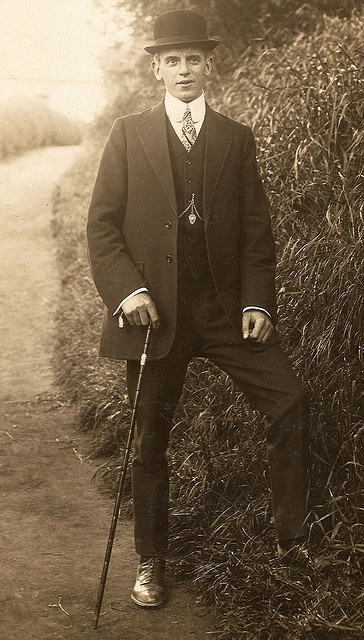 A smartly-dressed man standing in a country lane on a postally unused postcard.