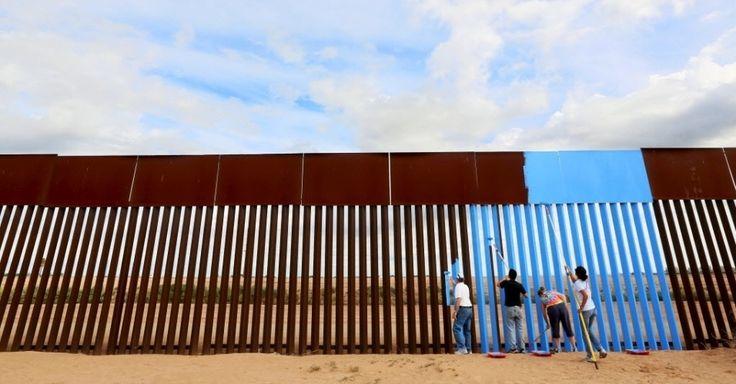"""20160409 - Um grupo de voluntários pinta de azul o lado mexicano da cerca que separa o país dos Estados Unidos. A pintura, feita neste sábado (9), faz parte de uma intervenção artística chamada """"Apagando a Fronteira"""" e tenta dar a ilusão de invisibilidade à cerca Imagem: Sandy Huffaker/Reuters"""