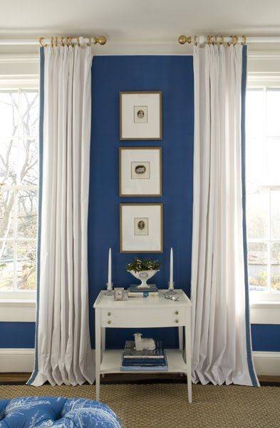 Bedroom by Kelley Proxmire with white curtains with blue trim and royal blue walls