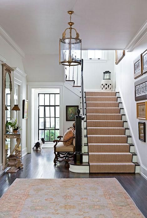 A large window at one end of this entry hall opens the space and floods it with gorgeous, natural light.