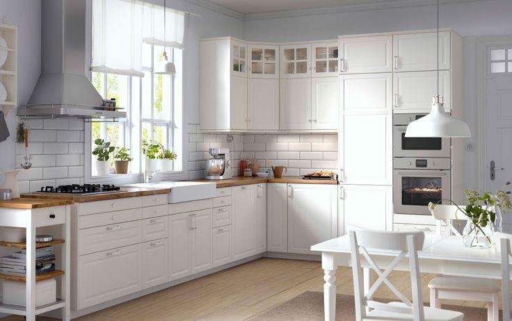 Traditionele keuken met witte kasten, houten werkbladen, vitrinedeuren en geïntegreerde toestellen