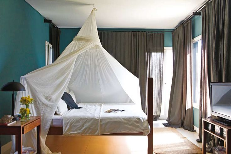 Dormitorio matrimonial minimalista con gran velo sobre la cama y cortinas oscuras generando intimidad.